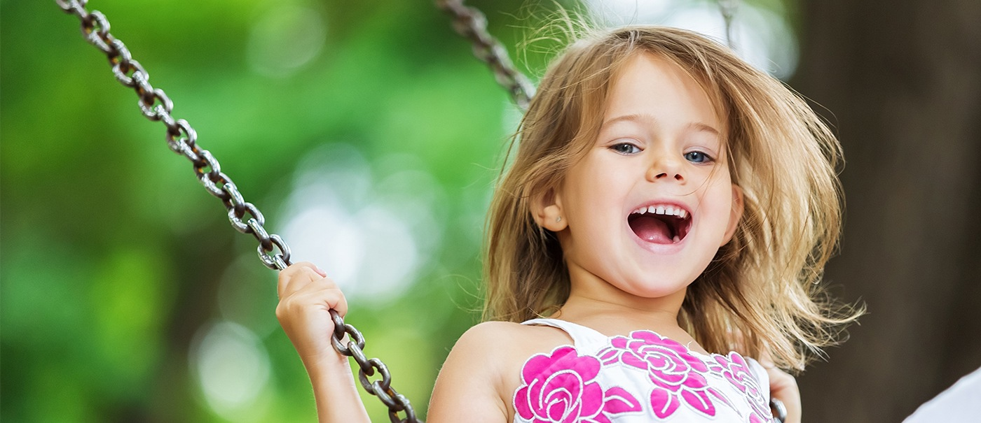 Little girl on a swing after children's dentistry visit