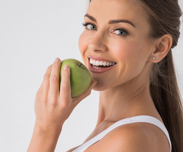 Woman eating a green apple after dental implant supported tooth replacement
