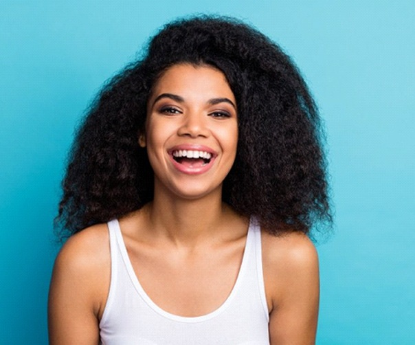 woman smiling with straight teeth thanks to Invisalign in Tyler, TX