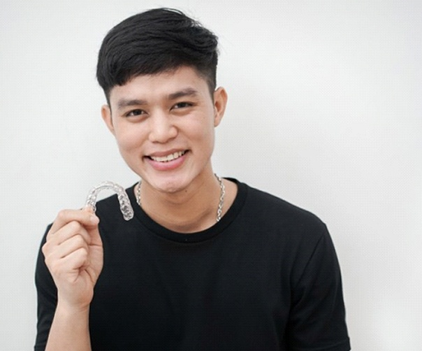 smiling young man holding Invisalign aligner