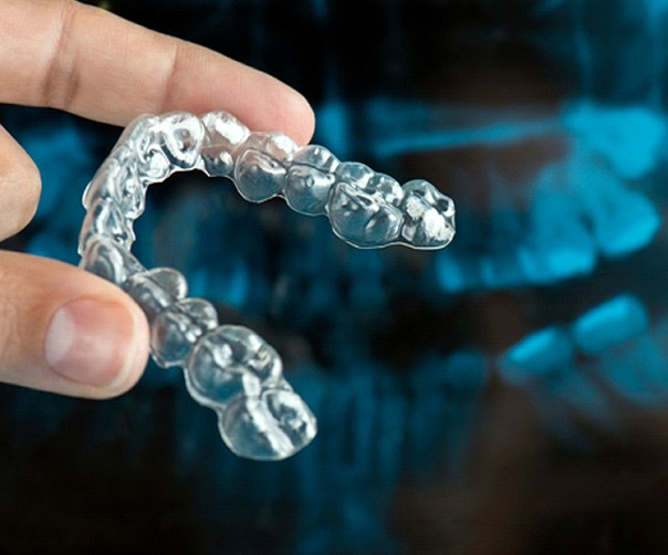close up of a hand holding an Invisalign aligner