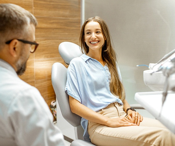 Patient and dentist smiling at each other during veneers appointment